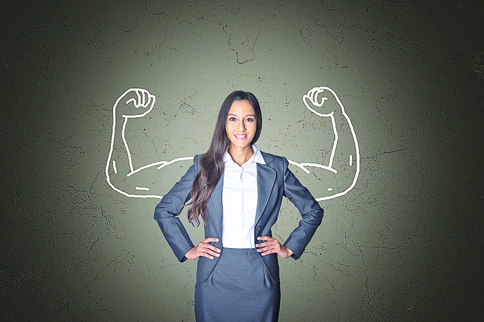 Conceptual Smiling Young Businesswoman Standing in Front Gray Gr