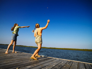 Two Girls Throwing Stones in Water